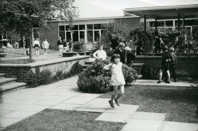 Girl jumping across a paved path in the playground, Woodside Junior School. c1960