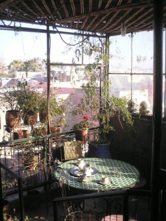 Sunlit veranda of coffee-house with cups on round table and flower pots on rails.