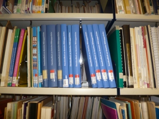 Tall blue volumes on library shelves.