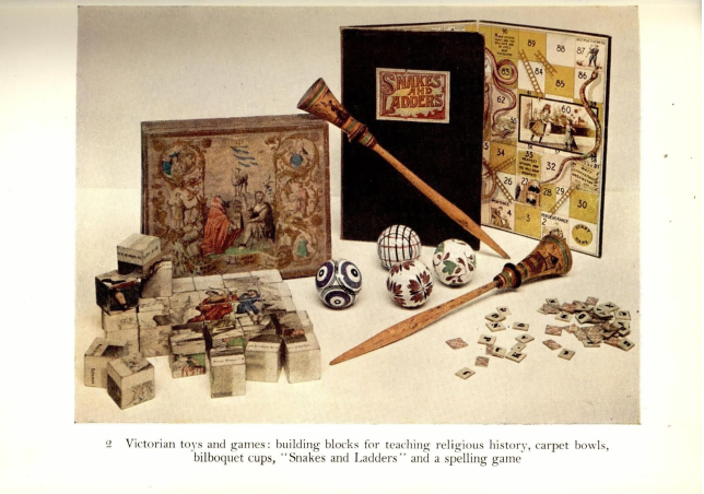 Colour photograph of Victorian toys, including a board game and 'carpet bowls'.