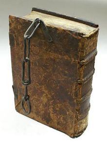 Massive leather-bound book with short iron chain attached to it.