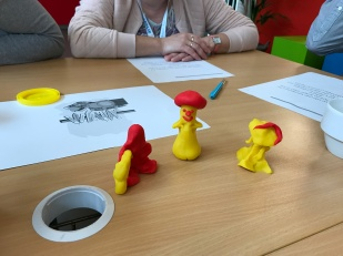 Three little playdough figures in bright yellow and red on a desk.