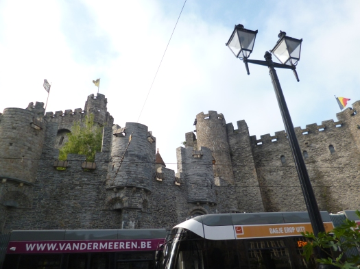 Mediaeval castle with trams going by underneath battlements.