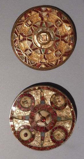 Round brooches with circular ornaments in gold and garnet, also glass and shell.