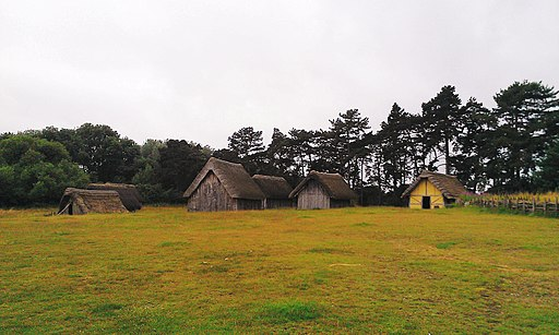 Very simple cottages on meadow at edge of forest, in wood and thatch, some triangular.