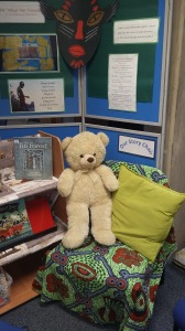 Large teddy-bear on armchair with bright blanket and cushion, between bookshelves..