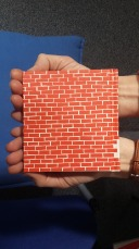 Tiny book looking like a brick wall, lying in a pair of hands.