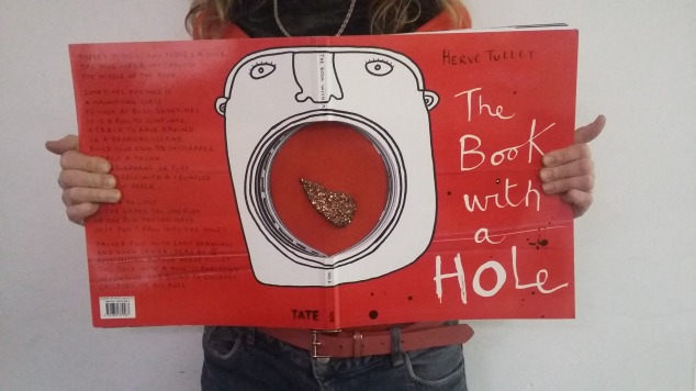 Huge book with hole, showing person behind; fruit on her jumper seems to be in mouth painted around the hole.