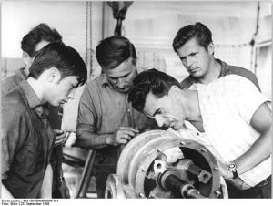 Five men working in factory. Black-and-white photo of 1968.