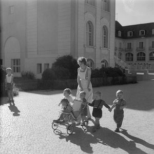 Woman looking after five toddlers. Black-and-white photo of ca. 1963.
