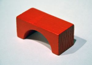 Simple red toy block in the shape of a bridge.