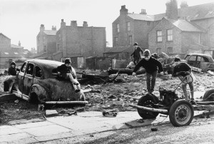 Children playing with wrecked cars between bleak brick houses.