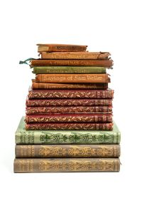 Pile of tiny books with golden ornaments on the spines.